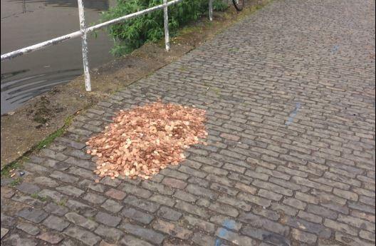 英国艺术家在马路上撒下15000枚硬币 路人的反应是这样……