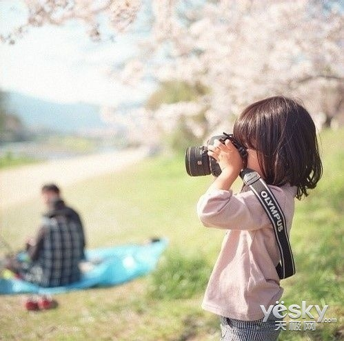 一个小女孩拿着相机拍照.