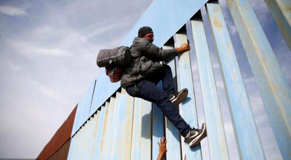 移民持续抵达美墨边境 徒手攀爬边境隔离墙